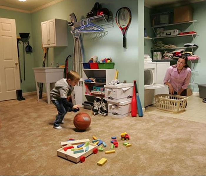 A clean basement, playroom and laundry room with a child playing