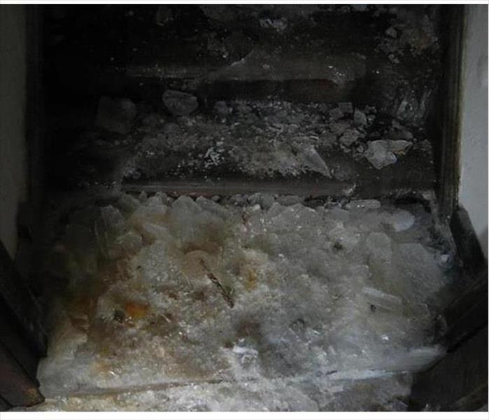 ice heaped on a stairwell leading to a cellar