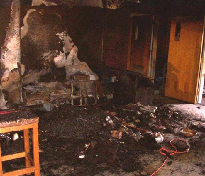 Fire damage in a class room has destroyed furniture and covered the room in soot.