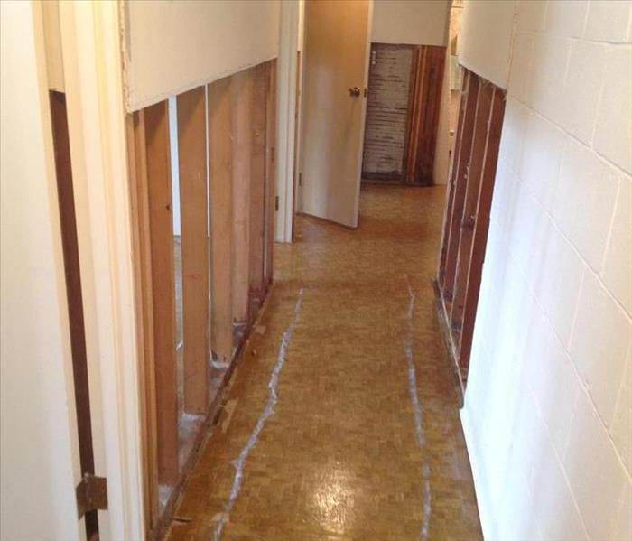 Damaged hallway, the sheetrock has been cut from the floor and drying equipment is in place.