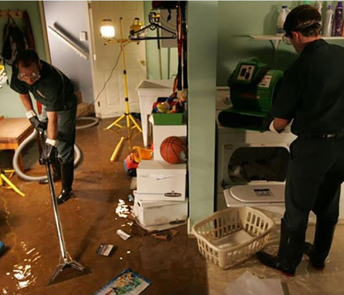 Flooded basement playroom and laundry room. Water covers the floor and belongs in the area.