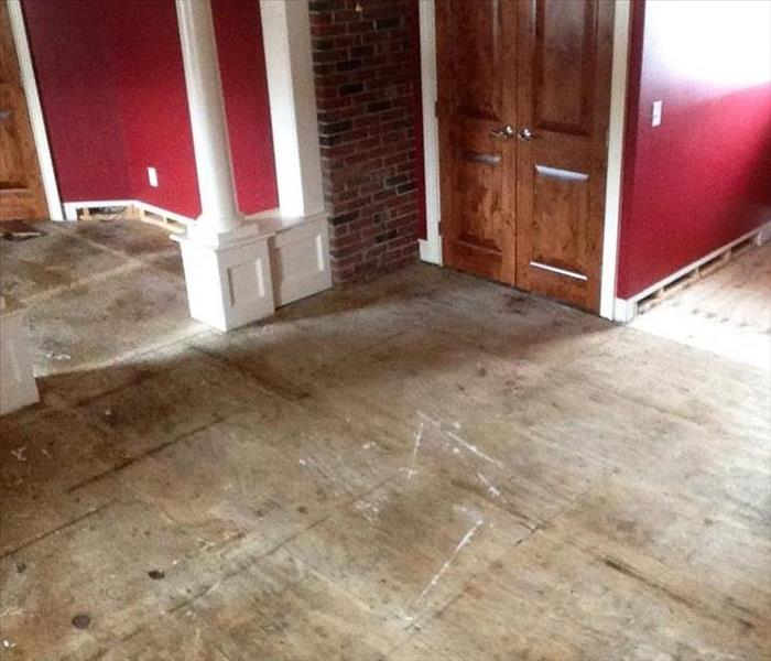 Restoring a multi-family home, the floors have been removed and the walls are freshly painted.