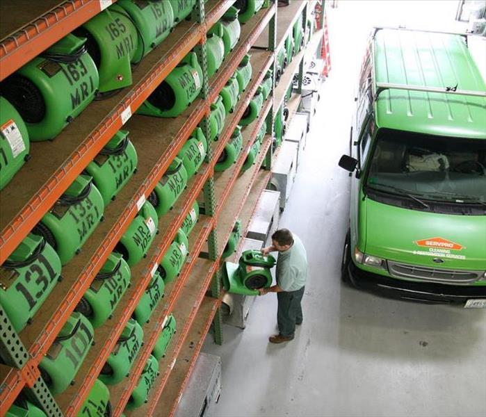 SERVPRO employee removing an air mover from the shelf to load into a van.